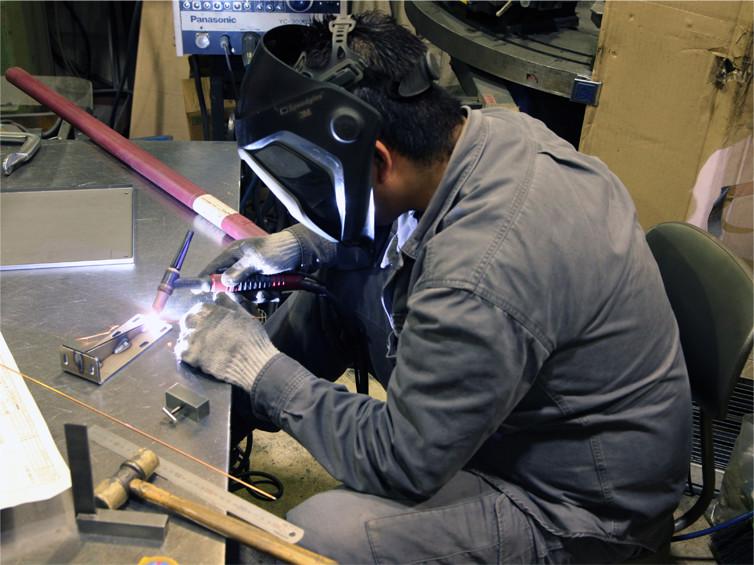 溶接治具を用いて、バンドソーにてカットした丸パイプ(SUS)とレーザー加工機にて切断加工したプレート(SUS)の溶接